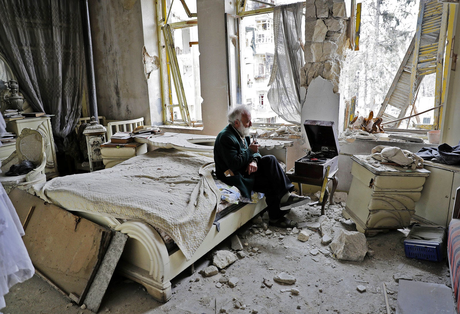 Mohammed Mohiedin Anis, 70, smokes his pipe as he sits in his destroyed bedroom listening to music on his vinyl player, in Aleppo's formerly rebel-held al-Shaar neighborhood on March 9.
