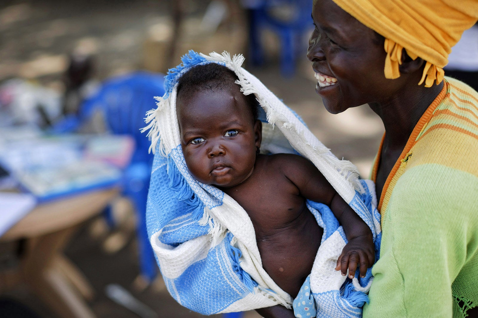 South Sudanese refugee Betty Sakala, from Central Equatoria state, laughs after being shown a photo of her daughter Mary, 2 months, as she waits to have Mary examined at a mobile health clinic run by the International Rescue Committee, in Bidi Bidi, Uganda, on June 5.