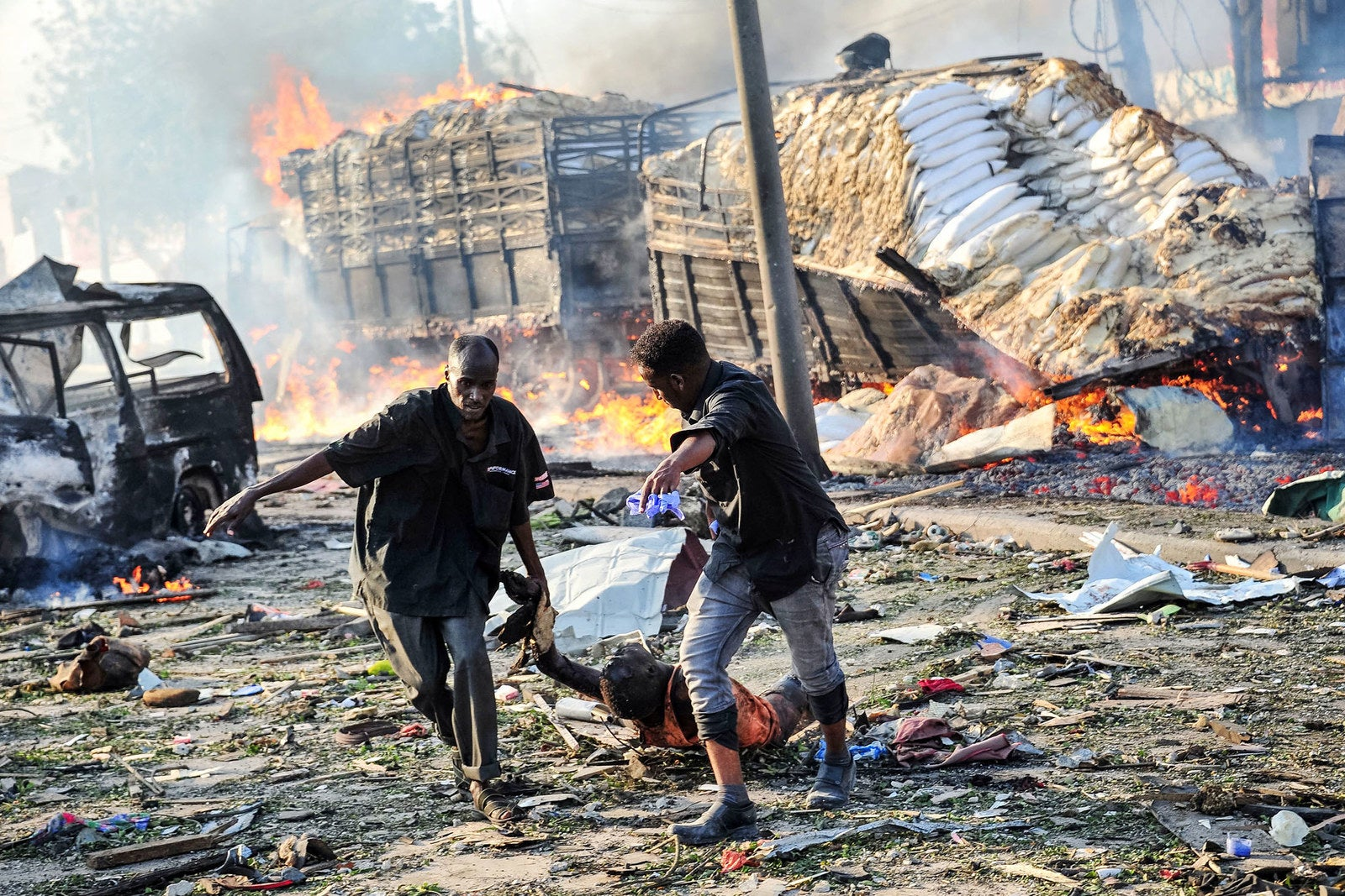 Two men carry the body of a victim following the explosion of a truck bomb in the center of Mogadishu, Somalia, on Oct. 14.