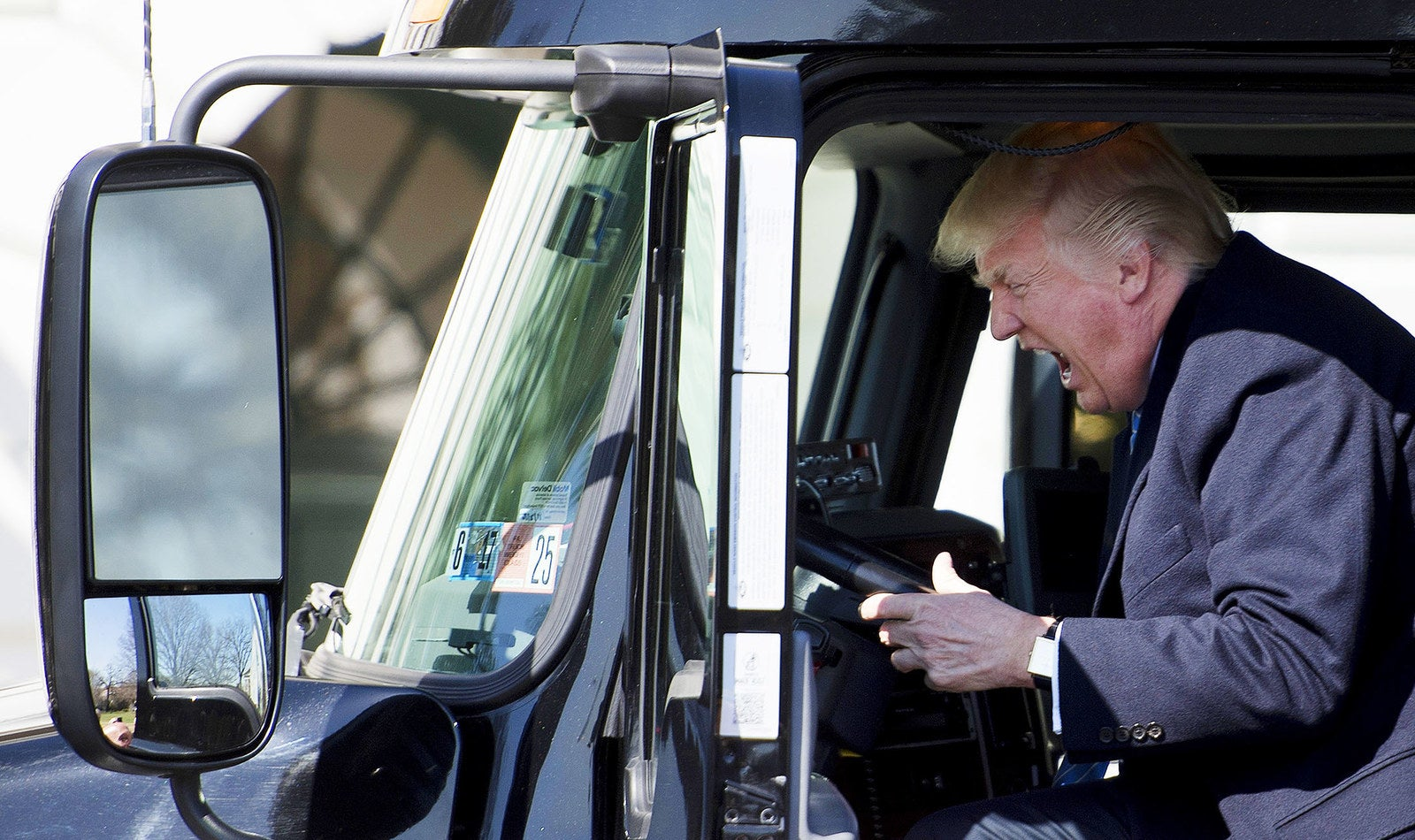 President Trump pretends to drive as he gets in an 18-wheeler and meets with truckers and CEOs regarding health care at the White House on March 23.