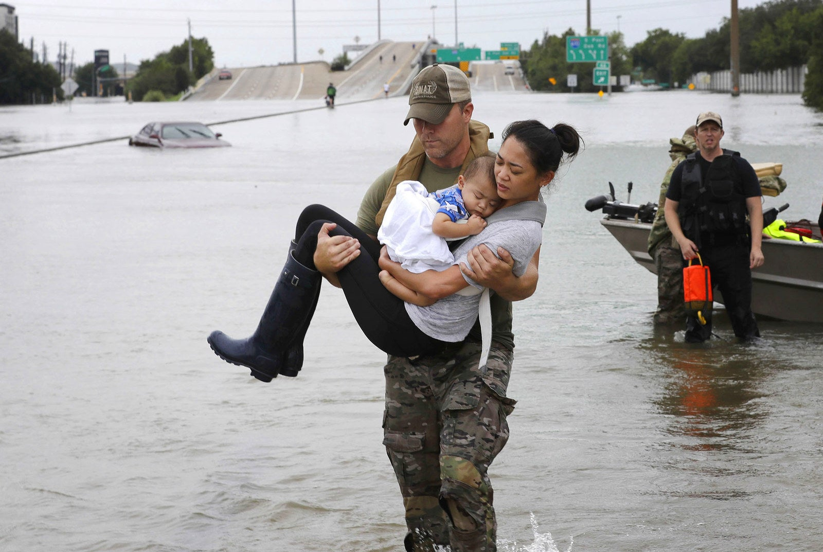 Houston Police SWAT officer Daryl Hudeck carries Catherine Pham and her 13-month-old son Aiden after rescuing them from their home surrounded by floodwaters from Tropical Storm Harvey on Aug. 27, in Houston.
