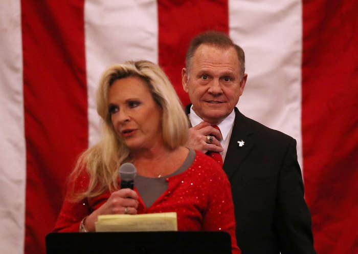 Republican Senate candidate Roy Moore stands behind his wife, Kayla, as she speaks during a campaign event Monday night in Midland City, Alabama.