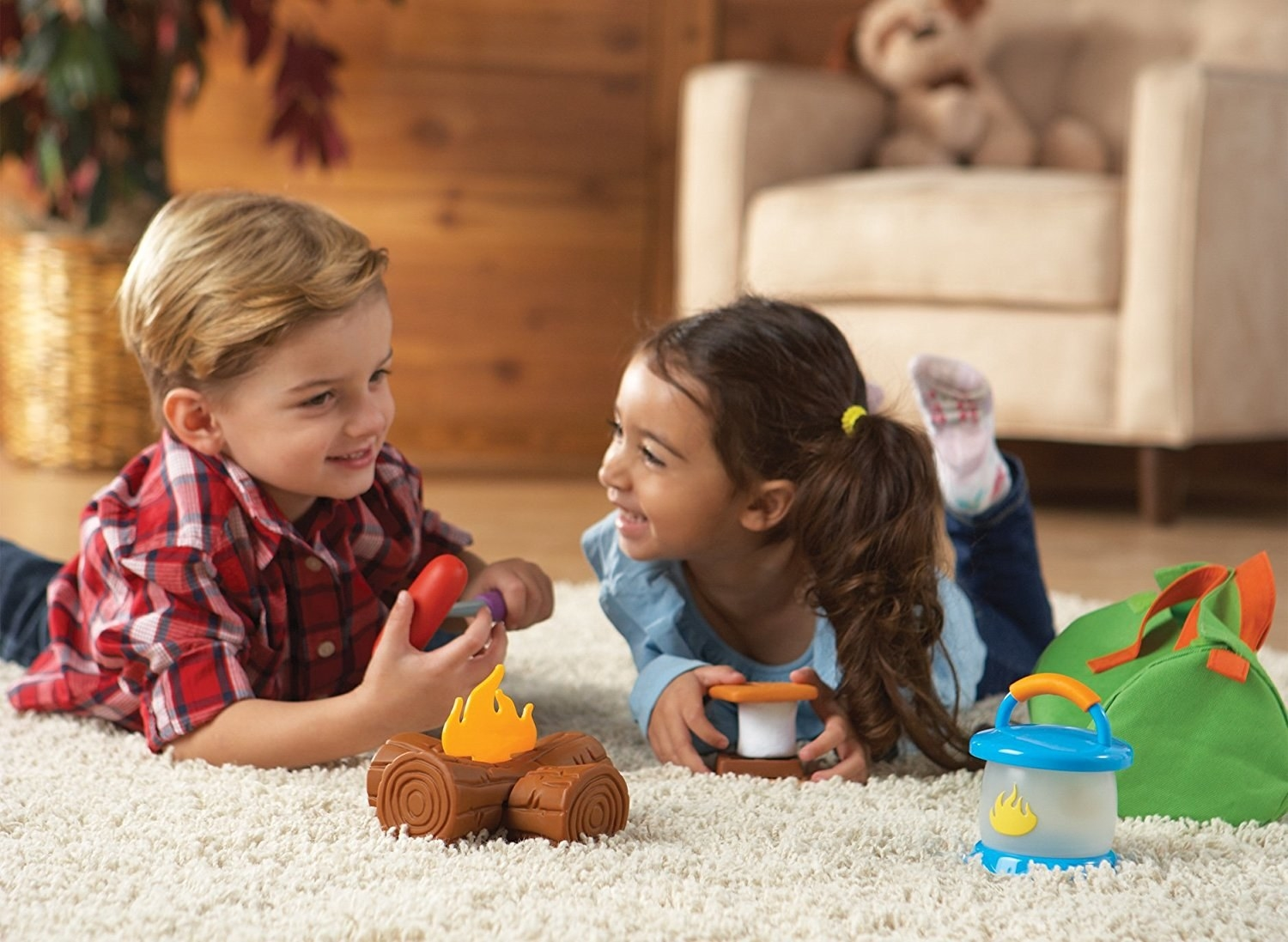two kids playing with plastic campfire, smores, and lantern