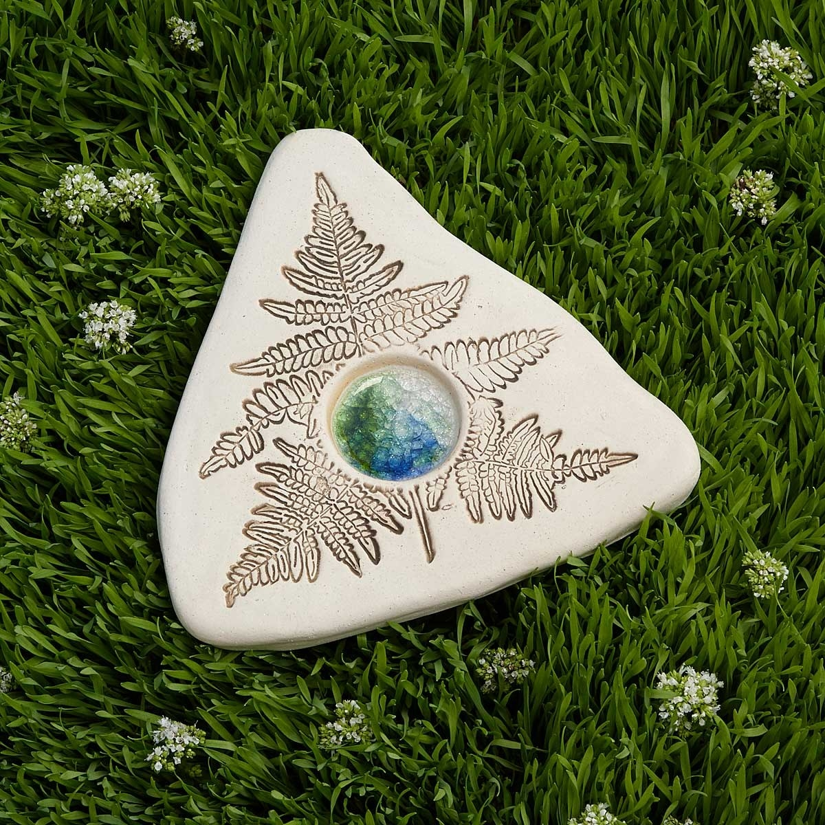 triangle shape stone with leaf prints on it and a water puddle in the middle