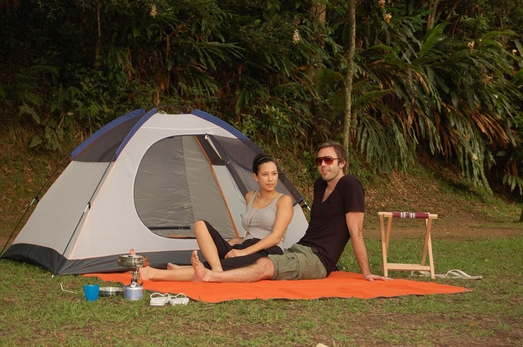 people sitting on the mat in front of a camping tent