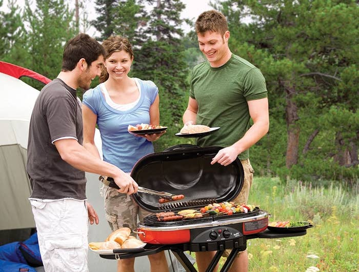 three people using the small portable grill to make kabobs and hot dogs beside of a camping tent
