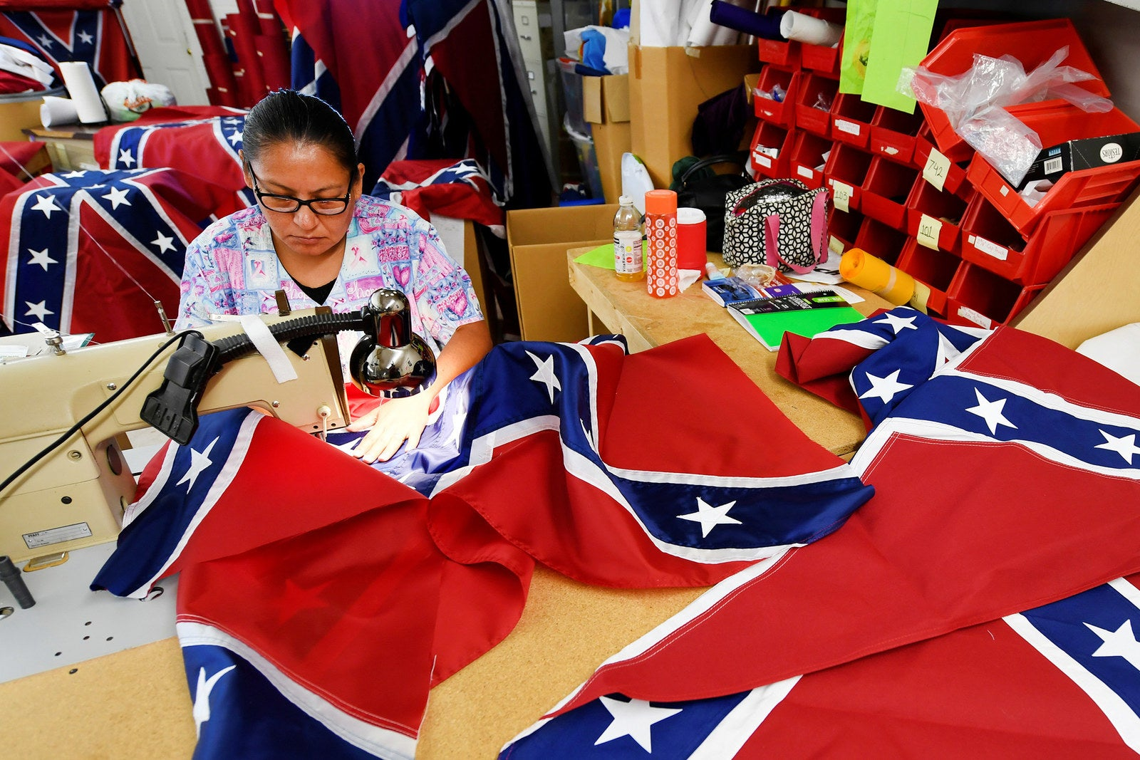 Blanca Hernandez sews stars on a Confederate battle flag in the Alabama Flag & Banner shop in Huntsville, Alabama, on Aug. 24.