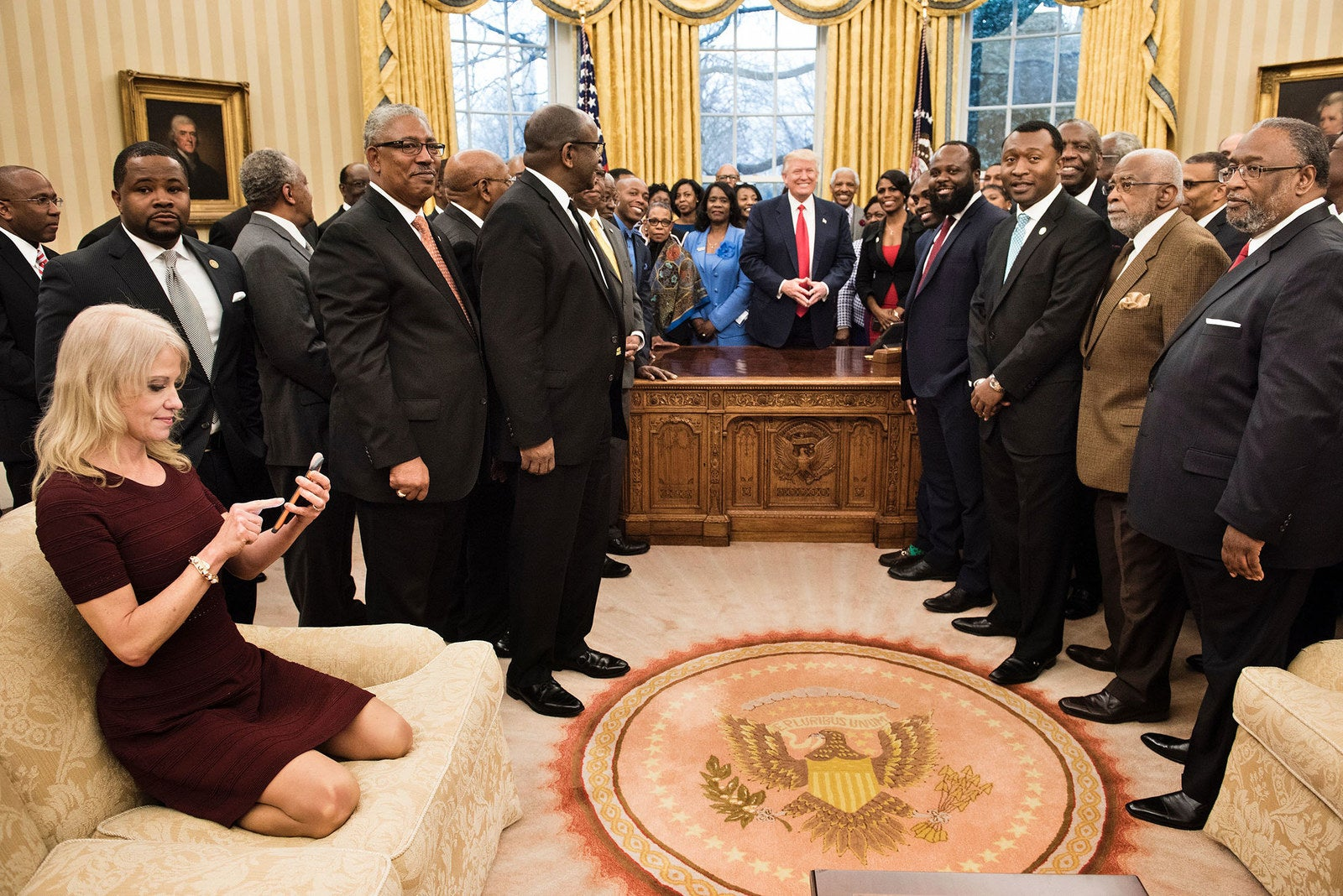 Kellyanne Conway, counselor to the president, checks her phone as President Donald Trump and leaders of historically black colleges and universities pose for a group photo in the Oval Office on Feb. 27.