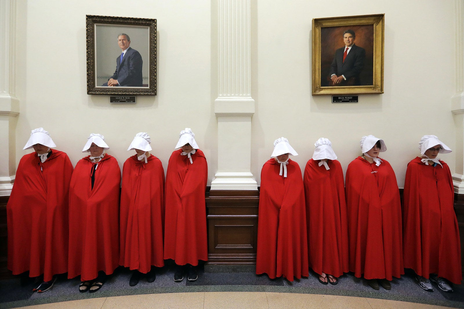 """Protesters dressed as characters from The Handmaid's Tale chant in the Texas Capitol Rotunda under portraits of former Texas governors George W. Bush and Rick Perry in Austin on July 18. State lawmakers began a special legislative session to tackle conservative priorities that stalled previously; chief among them, a """"bathroom bill"""" targeting transgender people."""