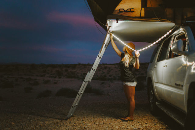 person stringing up the light string beside of a truck for camping
