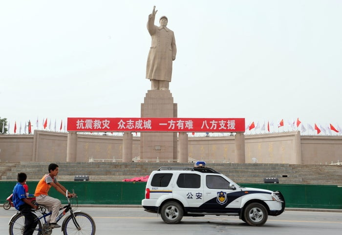 A police vehicle and Uighur boys on a bicycle pass the statue of Communist China's former leader Mao Zedong in Xinjiang.