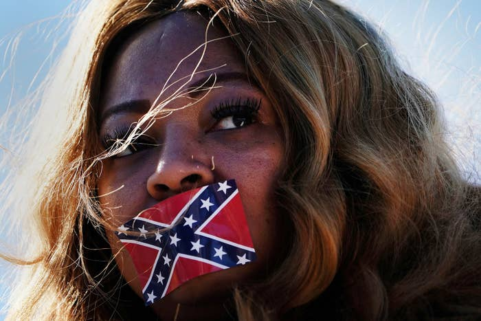 Edelia Carthan stands in protest with a confederate flag sticker covering her mouth during the official opening ceremony for the Mississippi Civil Rights Museum in Jackson, Mississippi, on Dec. 9.
