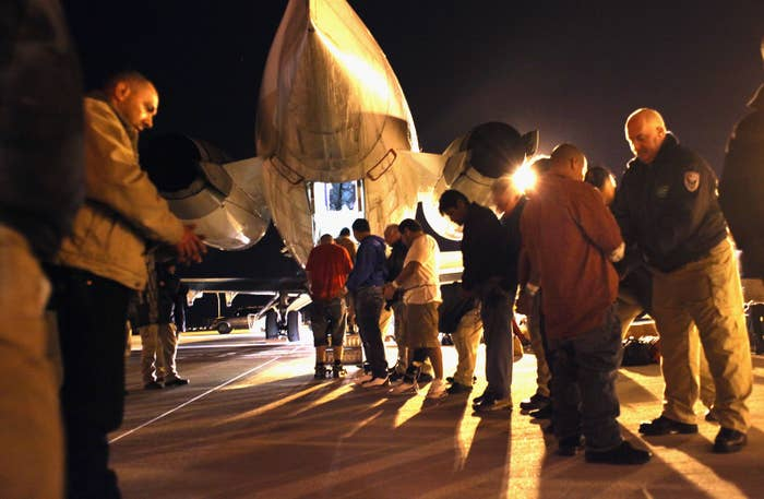 Immigration and Customs Enforcement officers pat down undocumented immigrants from El Salvador before boarding them onto a deportation flight on Dec. 8, 2010 in Mesa, Arizona.