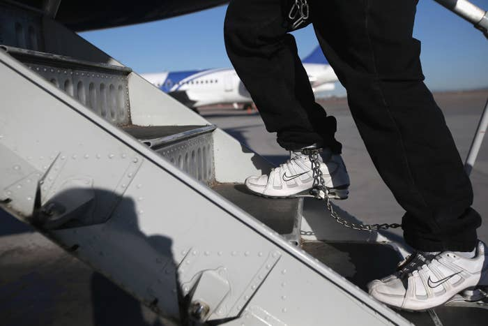 A Honduran immigration detainee, his feet shackled and shoes laceless as a security precaution, boards a deportation flight to San Pedro Sula, Honduras, on Feb. 28, 2013.