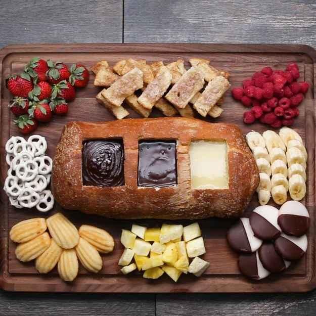 12 porçõesVocê vai precisar de:1 pão grande4 colheres de sopa de manteiga3 colheres de sopa de manteiga1/2 colher de sopa de canela285g de chocolate meio amargo285g de chocolate ao leite285g de chocolate branco765ml (3 1/4 copos) de creme de leite, distribuídasModo de preparo:1. Preaqueça o forno a 180ºC2. Em uma tábua de corte, corte 3 quadrados igualmente espaçados, de aproximadamente metade da largura e 1/6 do comprimento do pão.3. Pegue as 3 sobras do corte do pão e fatie em 6 tiras cada uma.4. Em uma assadeira forrada com papel manteiga, coloque o pão e as tiras das sobras.5. Misture manteiga e açúcar, e pincele o pão.6. Adicione canela à mistura de açúcar com manteiga e pincele as tiras.7. Leve ao forno por 25 minutos, removendo as tiras torradas de canela após 10 minutos.8. Em uma pequena panela, misture chocolate meio amargo e 1 1/4 copos (295ml) de creme de leite, e mexa até incorporar totalmente.9. Em uma pequena panela, misture chocolate ao leite e 1 copo (235ml) de creme de leite, e mexa até incorporar totalmente.10. Em uma pequena panela, misture chocolate branco e o que restou do creme de leite, e mexa até incorporar totalmente.11. Coloque o pão em uma travessa e encha cada buraco com um dos três fondues.12. Aproveite!Inspirado em:https://www.facebook.com/ChefClub.tv/videos/1419951341362808/