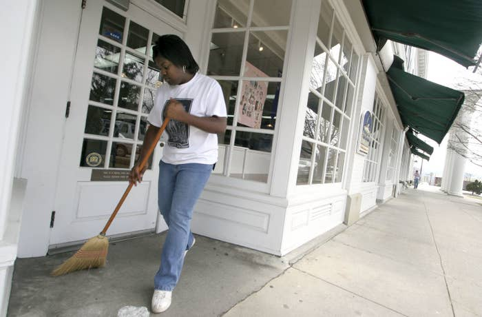Brittany Bonner, a first-year student at Berea College, sweeps outside the front door of the Berea College bookstore in Berea, Kentucky.