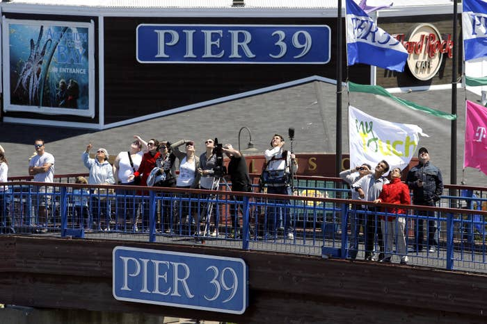 People gather to watch synchronized skydivers land at Pier 39.