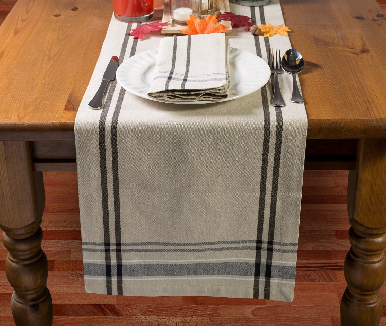 wood dining table with burlap stripe runner on it
