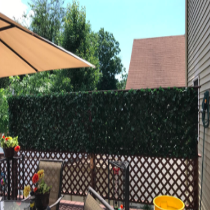 reviewer pic of faux ivy on top part of fence for some privacy in a backyard