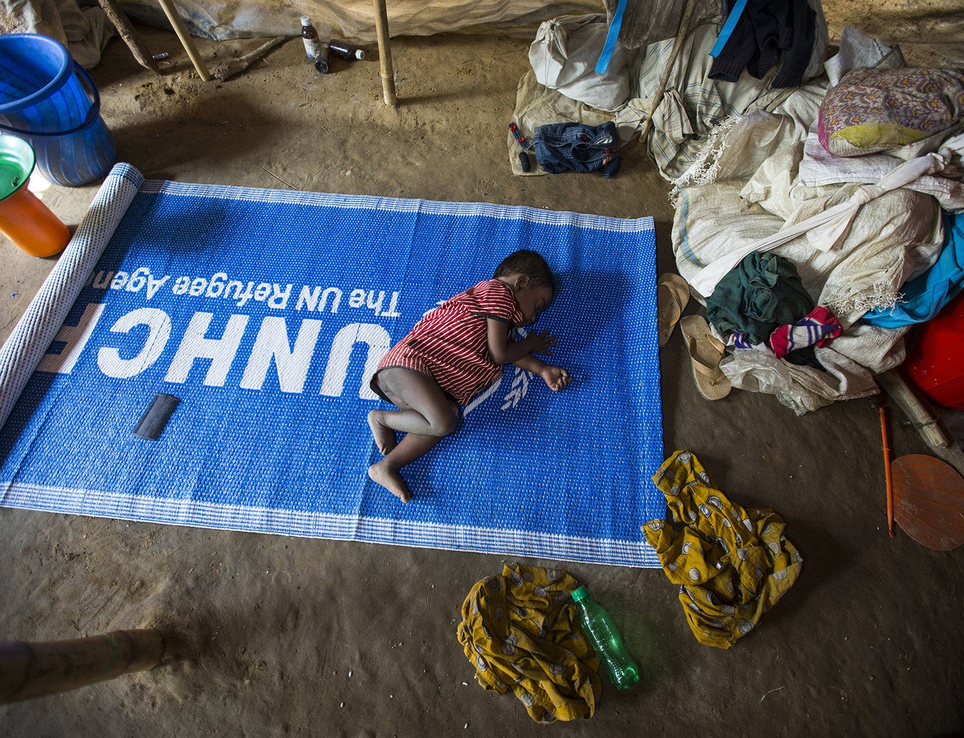 A child sleeps on a United Nations High Commissioner for Refugees mat at a refugee camp in Cox's Bazar, Bangladesh, on Dec. 27.