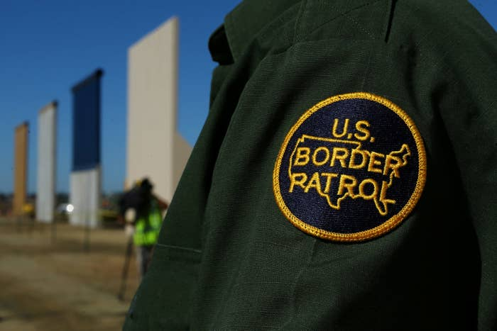 A Border Patrol officer next to prototypes of a border wall.