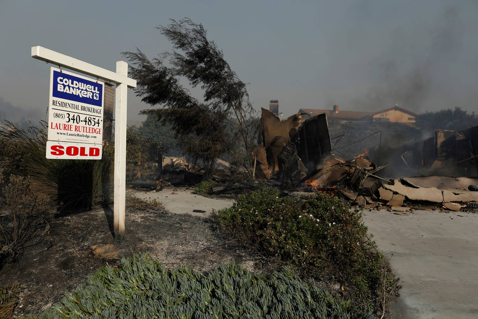 A Real Estate Sign Next To The Remains Of Destroyed Home