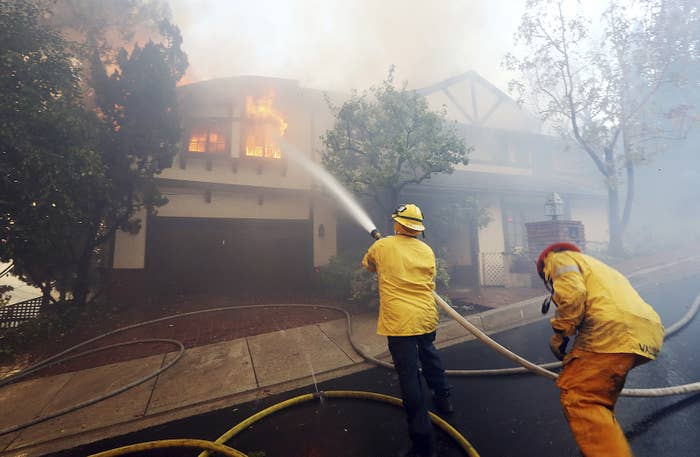 Los Angeles firefighters battle to contain flames to a burning home and prevent the fire's spread to adjoining properties in the Bel Air district of Los Angeles.