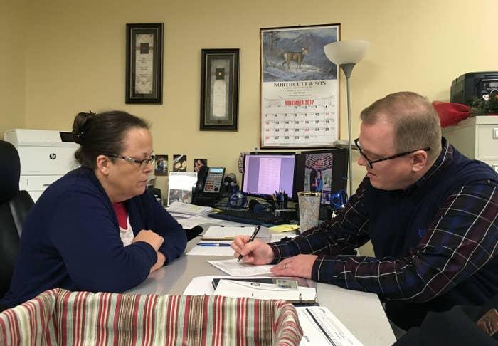 David Ermold filing his election paperwork on Wednesday as Kim Davis looks on.