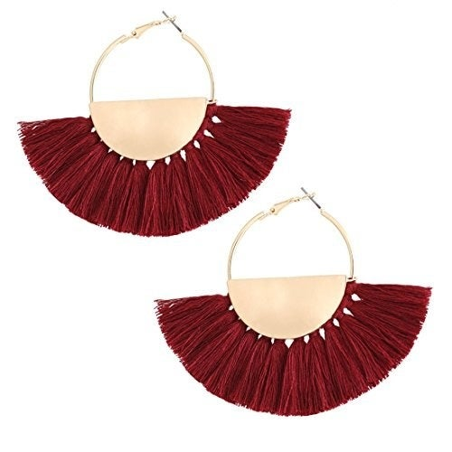 """Promising review: """"They seem to be well-made. The earrings have the snap tight closure, so you don't have to worry about them falling out. I think the metal is alloy base. The tassels are made of yarn. My sister really liked them. And they look beautiful on her."""" —Bridgette K. MahmoodGet them from Amazon for $9.99 (available in 20 colors)."""
