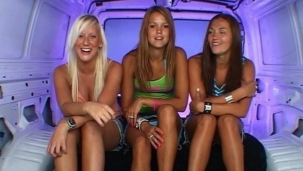 Three teen girls sitting inside the Room Raiders van while backlit with purple lighting