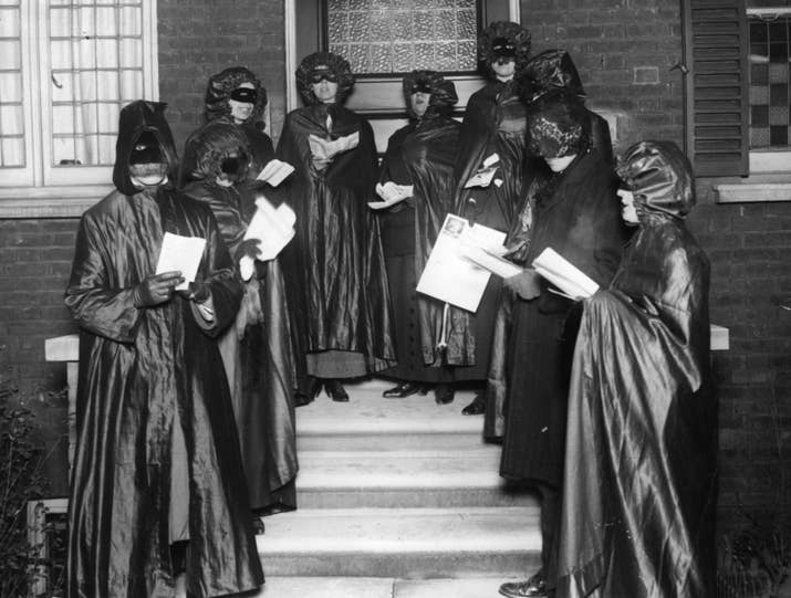 "Like these spooky bin bags, collecting in aid of a charity in 1910. The costumes are a throwback to a pagan tradition called ""mumming"", where revellers would wear disguises and visit neighbour's houses, singing and dancing in return for food, booze, and money."