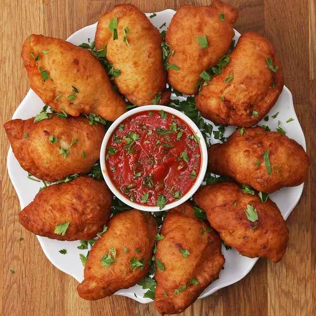 14 servingsINGREDIENTSPizza Dough320 mL (1 1/3 cups) warm water1 1/2 teaspoons active dry yeast435 g (3 1/2 cups) flour, divided25 g (1/4 cup) grated parmesan cheese1 teaspoon baking powder1 teaspoon salt2 teaspoons sugar3 tablespoons olive oil, dividedFilling520 g (2 cups) tomato sauce, divided300 g (3 cups) shredded mozzarella cheese, divided40 g (1 cup) basil, chopped, divided1  salt, to taste1  oil, for frying2 tablespoons parsley, chopped, to servePREPARATION1. In a liquid measuring cup, sprinkle the yeast over the warm water. Set aside for 5 minutes to bloom.2. In a bowl, add 3 cups of the flour, Parmesan, baking powder, salt, and sugar, and stir to combine.3. Add 2 tablespoons of the olive oil and stir to combine. Pour the yeast water over the flour mixture and stir until the dough forms into a ball.4. Use ¼ cup (30 grams) of flour for dusting the surface. Scrape the dough out of the bowl onto your floured surface. Knead the dough for about 10 minutes until the dough is tight and form the dough into a ball.5. Pour 1 tablespoon olive oil in a bowl. Place the dough in the bowl.6. Cover, let rise for 1 hour in a warm area, or until the dough has doubled in size.7. Flour the surface. Flip bowl over surface and let the dough fall out of the bowl. Cut the dough into 2-inch (5-cm) pieces. Roll into balls.8. Begin forming the dough into a circle about ½-inch (1 1/4-cm) thick and 5 inches(12-cm) wide, making sure the middle of the circle is not too thin. Repeat with the other balls of dough.9. Spoon 1 tablespoon of tomato sauce on to the center of the dough.10. Sprinkle 2 tablespoons mozzarella, then 1 tablespoon basil. Season with salt.11. Fold the dough over the fillings and seal. Pinch the edge of the dough together and fold back. Repeat with the rest of the dough.12. Heat 2 inches of oil until the temperature reaches 365˚F (185˚C).13. Fry the calzones 2 at a time for about 3 minutes on each side. Remove from oil and drain on a paper towel-lined plate.14. Place a b