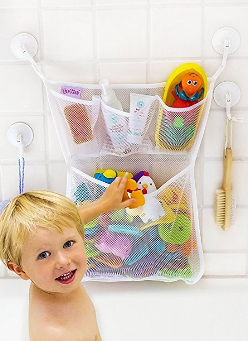 The mesh organizer containing bath toys and stuck to the wall