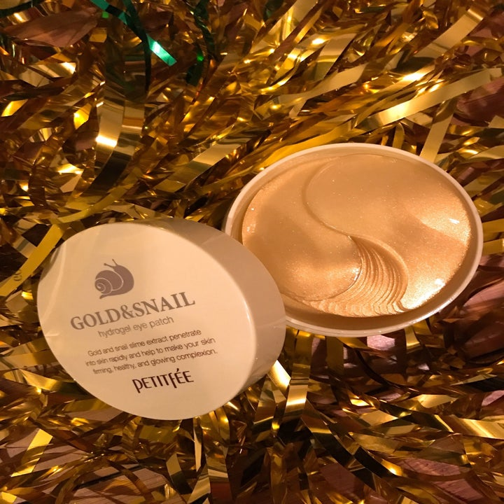 Jar of Gold & Snail Hydrogel Eye Patches on shimmery gold tinsel