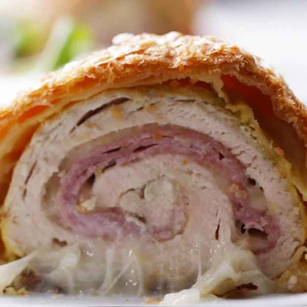 5 servingsINGREDIENTS4  boneless, skinless chicken breast1  salt, to taste1  pepper, to taste1 tablespoon garlic powder1 tablespoon onion powder16 slices swiss cheese75 g (1/2 lb) ham, sliced2 sheets puff pastry60 g (1/4 cup) english mustard1  egg, beatenPREPARATION1. Preheat oven to 400°F (200°C).2. Sprinkle the chicken breasts with salt, pepper, garlic powder, and onion powder, tossing to coat evenly.3. On a cutting board, place a chicken breast between two sheets of plastic wrap and pound until about ½-inch (1 cm) thick with a meat mallet, rolling pin, or heavy pan.4. Remove the plastic wrap and place a layer of Swiss cheese, then ham, then one more layer of Swiss cheese.5. Evenly roll the chicken, and place onto a new sheet of plastic wrap.6. Wrap the chicken in the plastic wrap, twist the excess plastic, and roll the chicken while twisting the sides in to tighten and firm up the roll of chicken cordon bleu. Tie the excess and chill in the fridge to set for 30 minutes.7. Cut the puff pastry sheets in half and gently roll out width-wise.8. Brush the pastry with mustard and place the chicken on to the bottom edge of the pastry.9. Tightly roll the chicken in the puff pastry, pinching the seams together to close and folding the sides under the bottom.10. Place the chickens rolls on a greased baking sheet and brush all sides with egg wash.11. With a fork, score a decorative design onto the surface of the puff pastry.12. Sprinkle with salt.13. Bake for 35- 40 minutes or until the puff pastry is a dark golden brown and the internal temperature of the beef is 165°F (75°C).14. Enjoy!