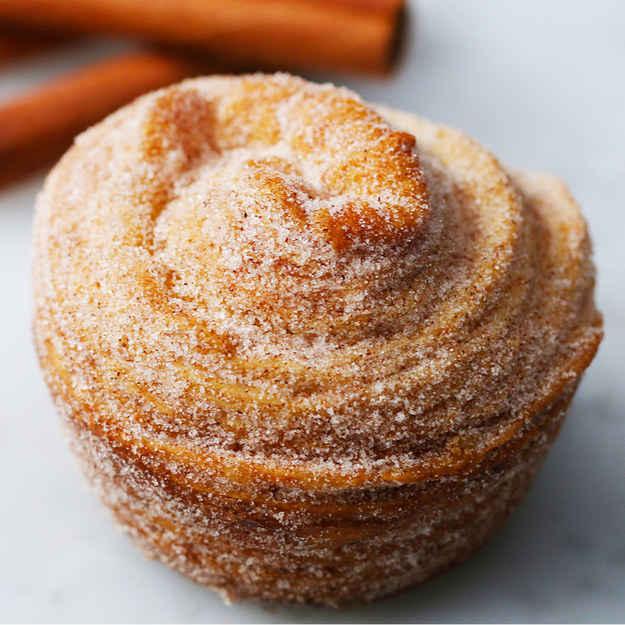 Bolo de aniversário de muffin de massa folhada8 porçõesVocê vai precisar de:2 folhas de massa folhada115g (1 ½ xícara) de manteiga amolecida1 ovo230g (1 xícara) de chocolate branco derretido15g (1 ½ xícara) de cereal de frutas90g (1 ½ xícara) de granulados sortidosModo de preparo:1. Preaqueça o forno a 180 °C.2. Corte as folhas da massa folhada ao meio e use um rolo para a abrir cada metade em 60cm de comprimento e 20cm de largura.3. Passe manteiga sobre a massa e cuidadosamente faça rolinhos bem apertados. Corte o rolinho ao meio no sentido do comprimento.4. Pegue cada metade e dobre a parte macia da massa para dentro, para criar um formato espiral.5. Coloque os espirais em uma forma de cupcake e pincele a parte de cima com ovo batido.6. Leve ao forno por 15 minutos na prateleira de cima, em seguida transfira para a de baixo e asse por mais 15 minutos.7. Tire do forno. Quando esfriar, mergulhe a parte de cima no chocolate branco derretido e então no cereal e nos granulados.8. Bom apetite!Inspirado por:http://baketotheroots.de/cruffins-croissant-meets-muffin/---Muffin de massa folhada de framboesa8 porçõesVocê vai precisar de:2 folhas de massa folhada115g (1 ½ xícara) de manteiga amolecida1 ovo160g (1 xícara) de geleia de framboesa8 framboesas80g (1 xícara) de açúcar de confeiteiroModo de preparo:1. Preaqueça o forno a 180°C.2. Corte as folhas da massa folhada ao meio e use um rolo para a abrir cada metade em 60cm de comprimento e 20cm de largura.3. Passe manteiga sobre a massa e cuidadosamente faça rolinhos bem apertados. Corte o rolinho ao meio no sentido do comprimento.4. Pegue cada metade e dobre a parte macia da massa para dentro, para criar um formato espiral.5. Coloque os espirais em uma forma de cupcake e pincele a parte de cima com ovo batido.6. Leve ao forno por 15 minutos na prateleira de cima, em seguida transfira para a de baixo e asse por mais 15 minutos.7. Tire do forno. Quando esfriar, corte o centro de cada cruffin e recheie com geleia de framboesa.