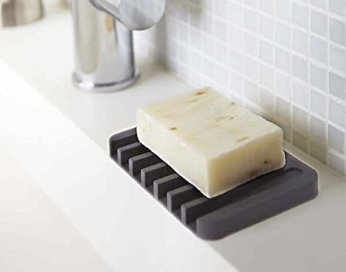 gray soap dish with slots for draining water into the sink