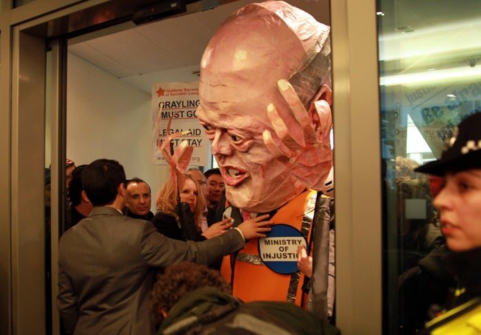 A legal aid cuts protester dressed as former justice secretary Chris Grayling.