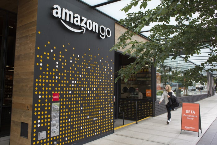 A woman walks past the Amazon Go grocery store at the Amazon corporate headquarters on June 16, 2017, in Seattle.