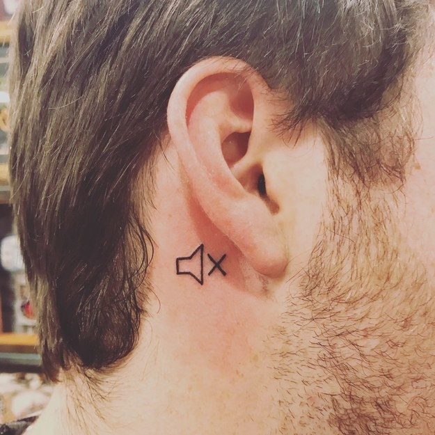 A tiny tattoo behind someone's ear of a music symbol with an 'X'