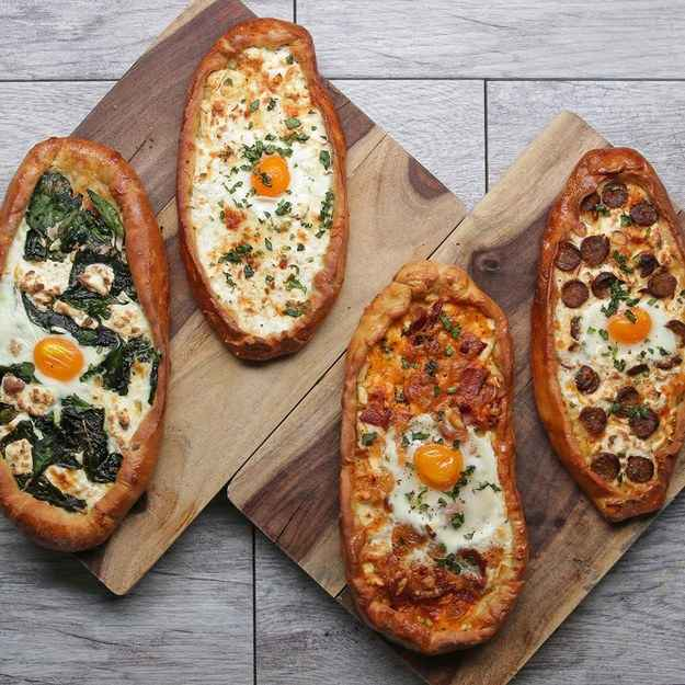 3 pizza boatsINGREDIENTS100 g (1 cup) shredded mozzarella cheese113 g (1 cup) feta cheese, crumbled450 g (1 lb) pizza dough, divided into 3 portions1 tablespoon olive oilEgg wash3  eggPREPARATION1. Preheat oven to 425˚F (220˚C).2. In a small mixing bowl combine the mozzarella and feta and set aside.3. On a large floured surface, roll out the pizza dough to an oval roughly 10 inches (25 centimeters) in length.4. Transfer the dough to a parchment paper-lined baking sheet.5. Cover surface of dough with olive oil and spoon on cheese mixture leaving a 1 inch margin around the outside of the dough.6. Fold in the 1 inch margin creating a crust around the cheese.7. Brush the crust with egg wash.8. Bake for 10 minutes.9. Remove the baking sheet from oven and with a knife spread out some of the melted cheese in the center of the pizza boat and crack an egg into it.10. Turn down heat to 400˚F (200˚C).11. Bake for an additional 6-8 minutes.12. Enjoy!