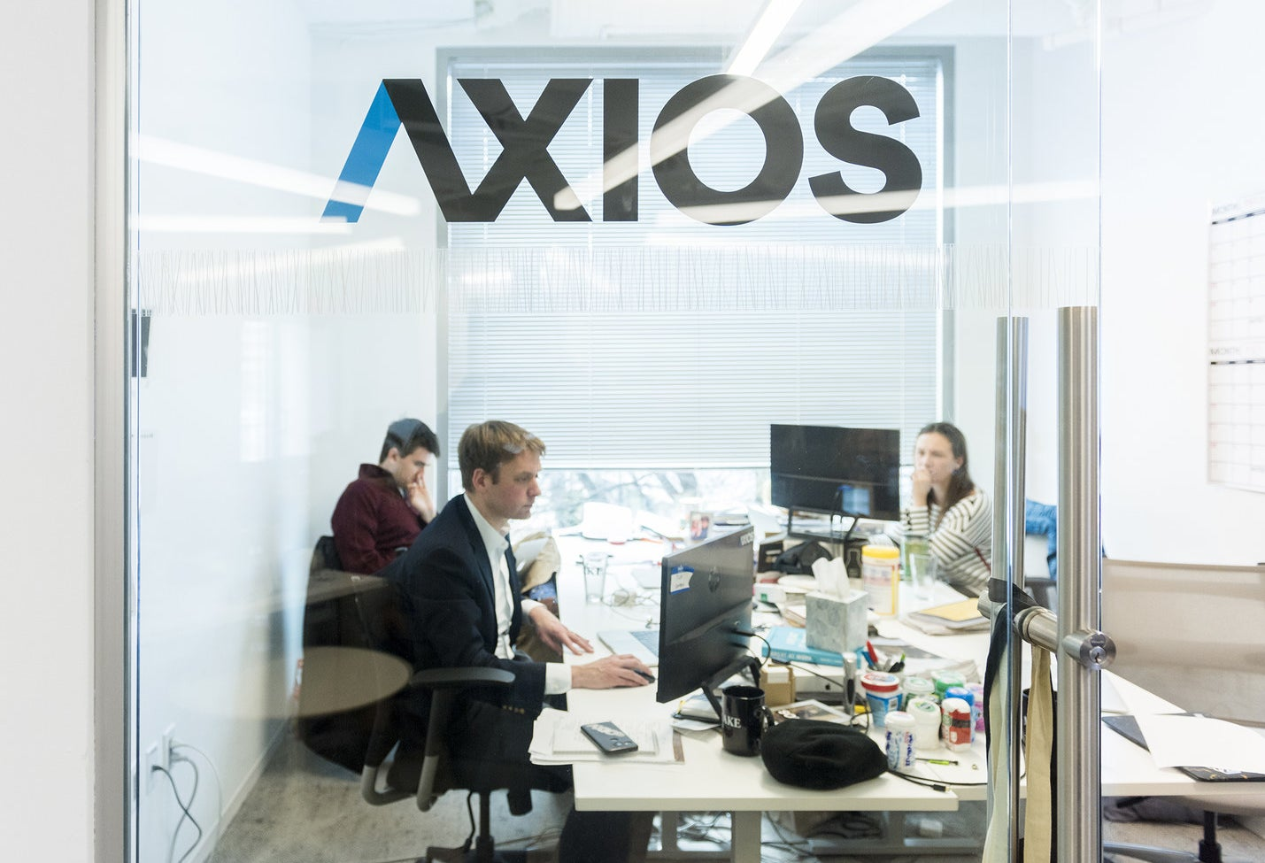 Editor Nicholas Johnston (center) in his office at Axios.
