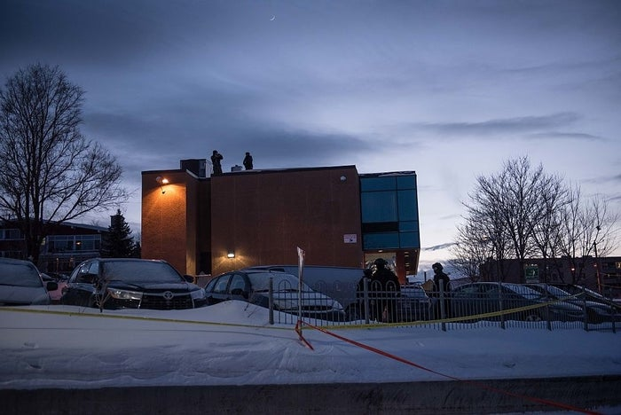 Police stand guard on the roof of the Islamic Cultural Center in Quebec City, Canada.
