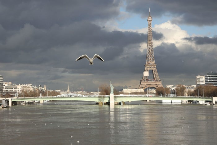 A picture taken on Friday shows the flooded Ile aux Cygnes and banks of the river Seine with a model of the Statue of Liberty and the Eiffel Tower in the background.
