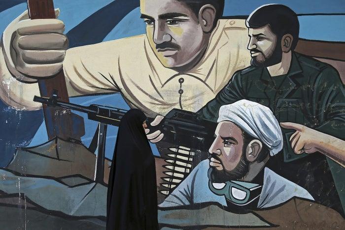 A woman walks past of a mural depicting members of Iran's Basij volunteer paramilitary force, in downtown Tehran.