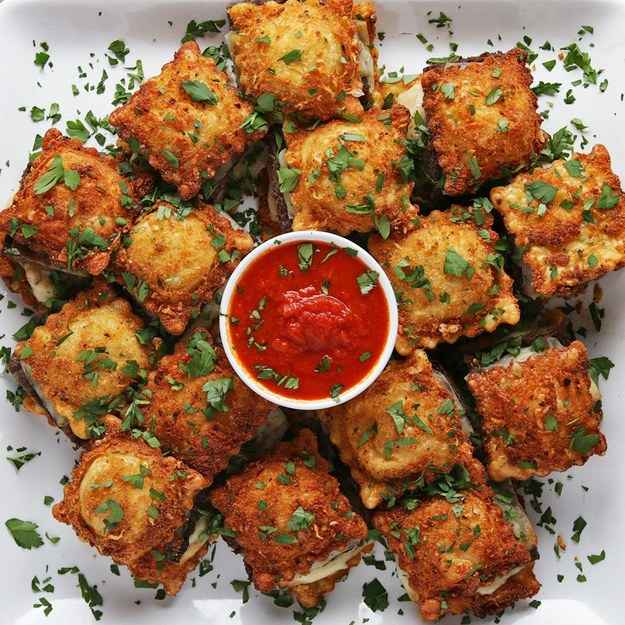 15 servingsINGREDIENTS455 g (1 lb) ground beef1 lb ground sausage1 teaspoon salt1 teaspoon pepper170 g (1 11/2 cups) italian breadcrumb1 tablespoon garlic powder1/2 teaspoon red pepper flake1 teaspoon salt110 g (1 cup) grated parmesan cheese2  egg, beaten30  ravioli, thawed if frozen oil, for frying15 slices mozzarella cheese, cut into fourths fresh parsley, to serve tomato sauce, to servePREPARATION1. Preheat oven to 350˚F (180˚C).2. In a bowl add the beef, sausage, salt, and pepper. Mix to combine.3. Spread the meat mixture onto a parchment paper-lined baking sheet.4. Bake for 10 to 15 minutes until fully cooked.5. In a bowl, add bread crumbs, garlic powder red pepper flakes, salt and Parmesan. Stir to combine.6. Take one ravioli and dip in the whisked eggs, then dip into the bread crumb mixture. Repeat with the rest of the ravioli.7. Heat 1 inch (2 cm) of oil until the temperature reaches 350˚F (180˚C). Fry ravioli 4 at a time.8. Cut the cooked meat into 15 pieces.9. Place the fried ravioli on a parchment paper-lined baking sheet in a ring shape. Place 2 squares of cheese on the ravioli. Place a piece of meat on top. Place 2 more squares of cheese on the meat. Place a ravioli on top.10. Bake for 5 minutes until cheese is melted.11. Sprinkle with parsley and serve with tomato sauce for dipping.12. Serve immediately.13. Enjoy!Inspired by:https://www.bettycrocker.com/recipes/fried-ravioli-with-marinara-sauce/51801a87-24b2-498a-9a7b-dfe9f2b633fc