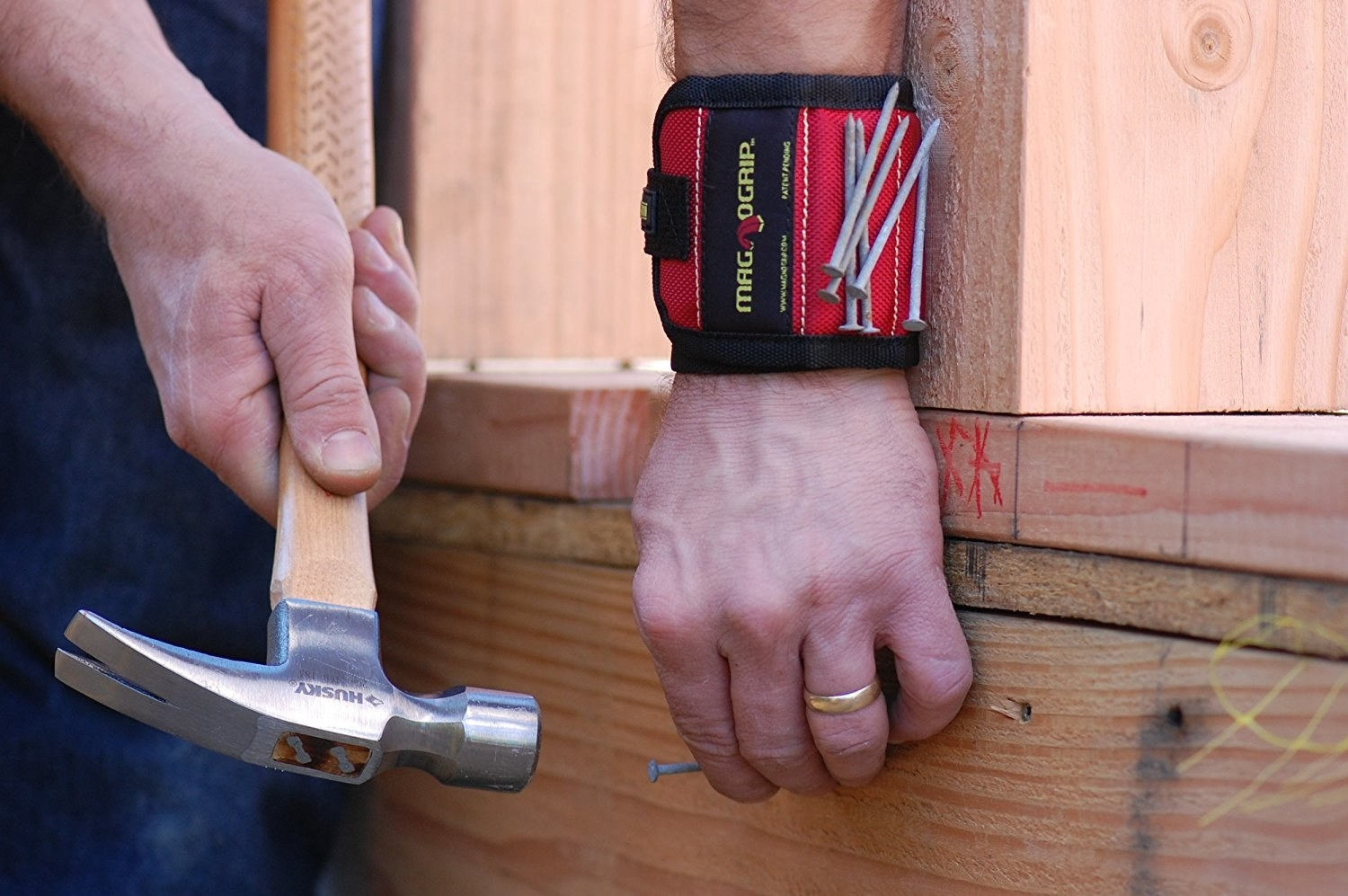 model wearing red wristband with nails stuck to it while they hammer one into wood