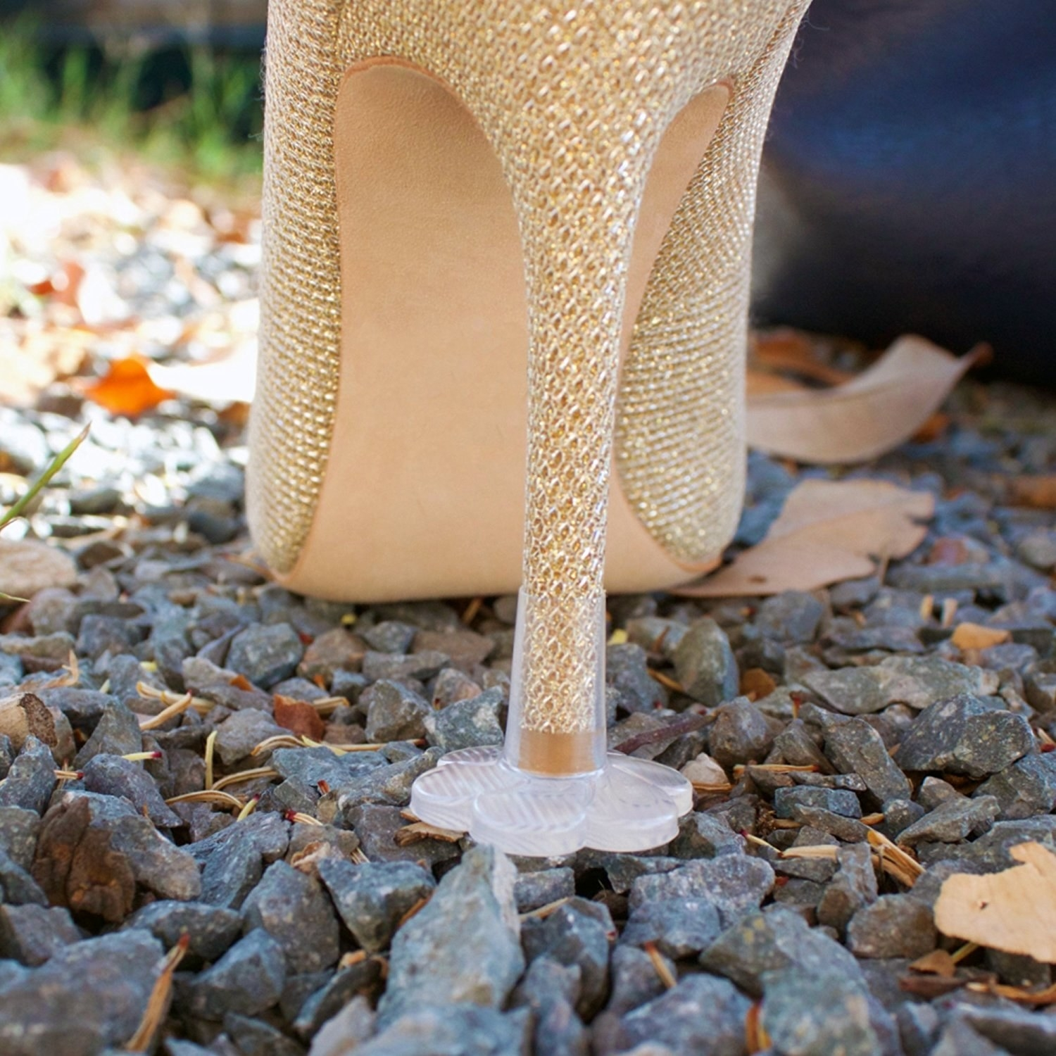 A shoe on gravel with a stopper over the tip of the thin heel. The stopper is transparent and has a flare, flower-shaped base