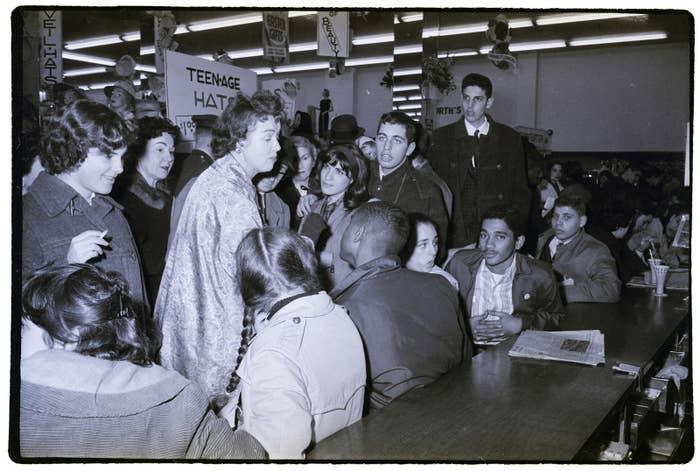 Eine Frau, die keinen leeren Platz an einer F.W. Woolworth Imbisstheke finden konnte, schlägt Demonstranten, die am 02. April 1960 an einem Sitzstreik teilnehmen.