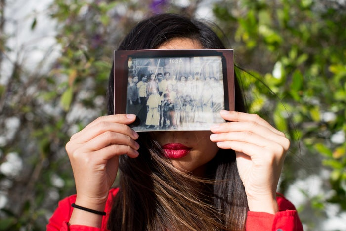 Anh holds a photograph of her immediate and extended family taken in 1973 in Vietnam.